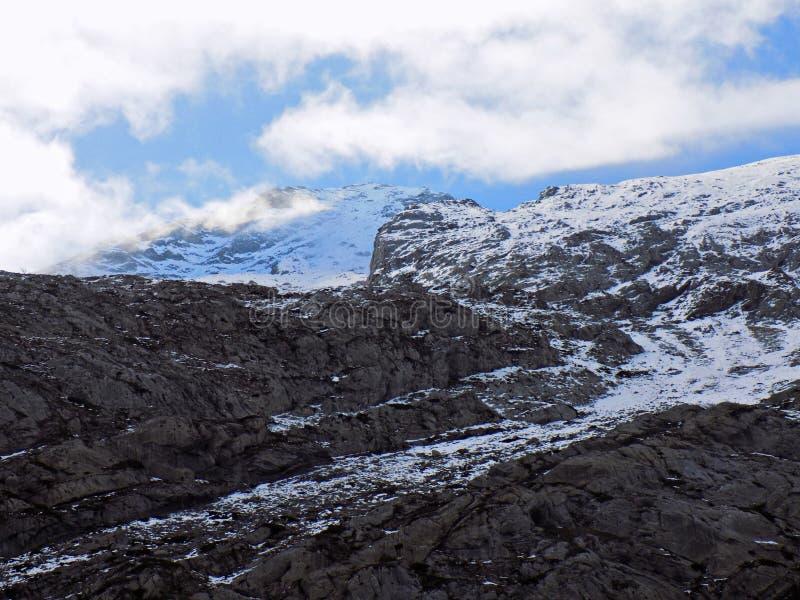 Picos rocosos y nubes nevosas fotografía de archivo