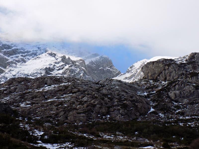 Picos rocosos y nubes nevosas fotos de archivo
