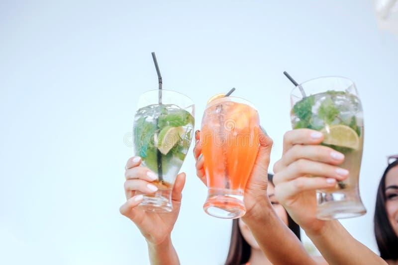 Pictire des femmes tiennent trois verres avec des cocktails Ils le montrent à l'appareil-photo Les brunes ont le repos images stock