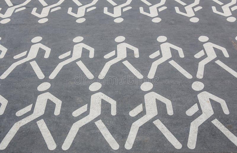 pictograms av folk som går i rader på asfalten royaltyfria foton