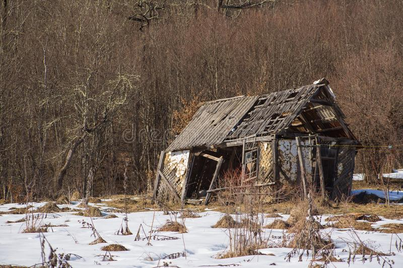 Pictorial landscape old dilapidated wooden small house stands alone in clearing with snow in mountains. On background of dense thickets royalty free stock photos