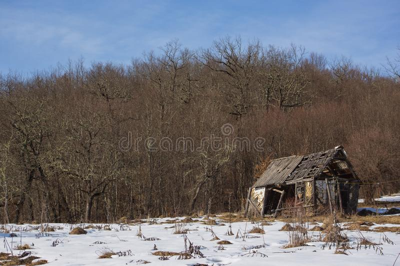 Pictorial landscape old dilapidated wooden small house stands alone in clearing with snow in mountains. On background of dense thickets under boundless blue sky royalty free stock images