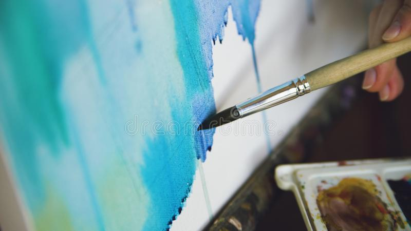 Pictrure da tração do artista da jovem mulher com pinturas da aquarela e escova na mão do close up da lona da armação imagem de stock