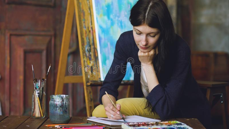 Pictrure del drenaje del artista de la mujer joven con las pinturas de la acuarela y cepillo en lona del caballete fotografía de archivo libre de regalías