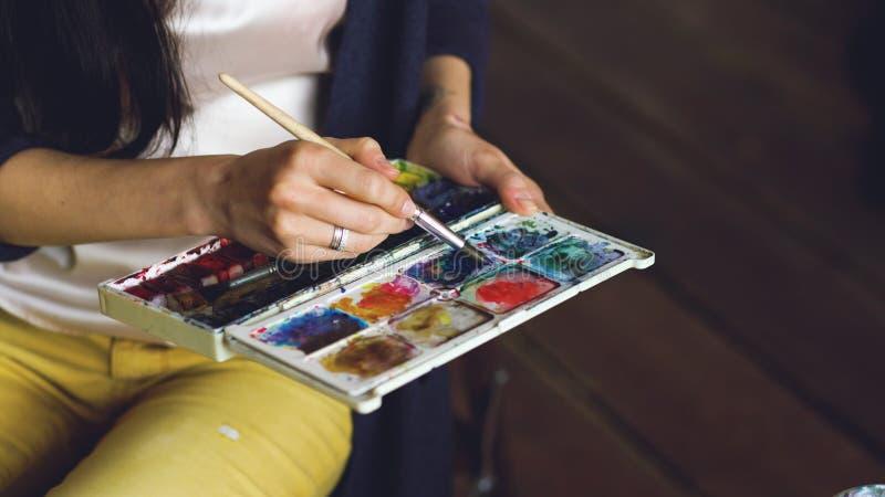 Pictrure del drenaje del artista de la mujer joven con las pinturas de la acuarela y el primer de mezcla de los colores del cepil fotos de archivo