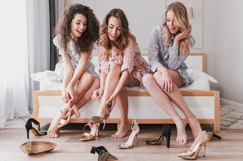 Picture of adorable stylish girls 20s wearing dresses trying on royalty free stock images