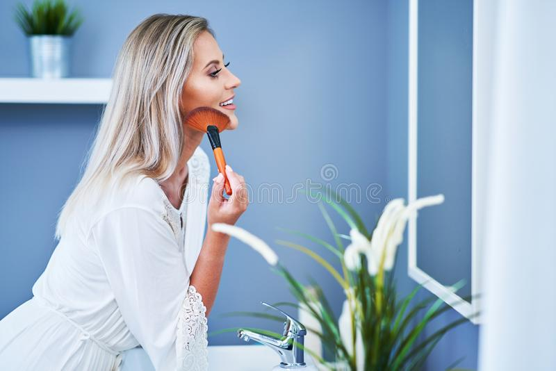 Beautiful brunette woman applying make-up in the bathroom. Picture of adult brunette woman in the bathroom royalty free stock photography