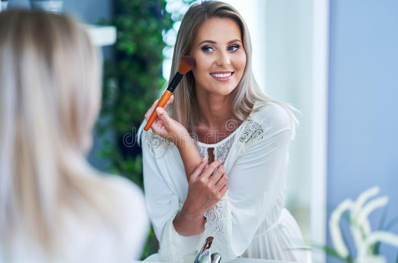Beautiful brunette woman applying make-up in the bathroom. Picture of adult brunette woman in the bathroom stock photo