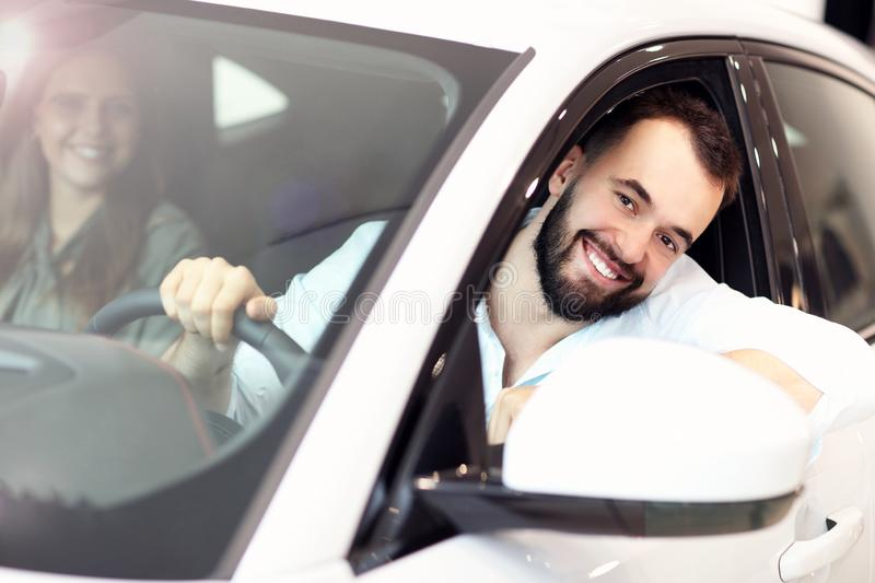Adult couple choosing new car in showroom. Picture of adult couple choosing new car in showroom stock images