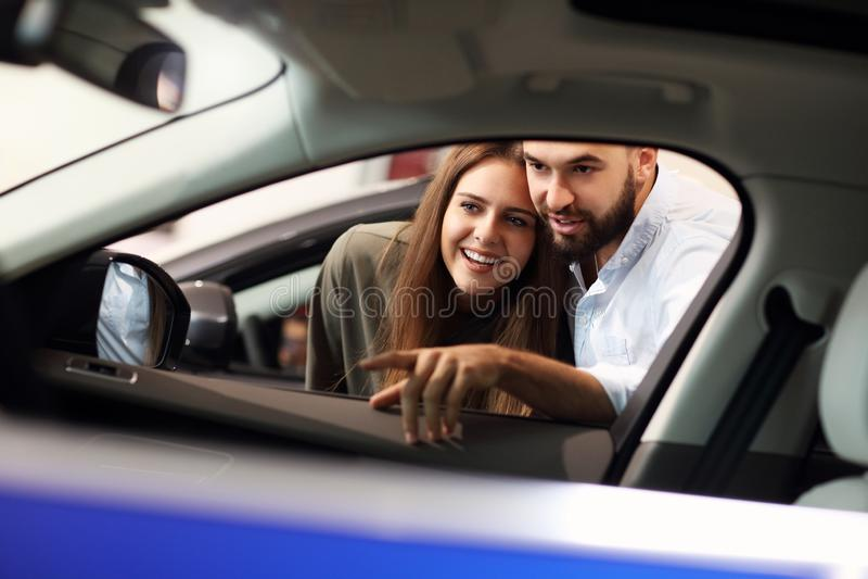 Adult couple choosing new car in showroom. Picture of adult couple choosing new car in showroom stock photo