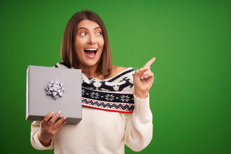 Adult happy woman with Christmas gift over green background stock photos