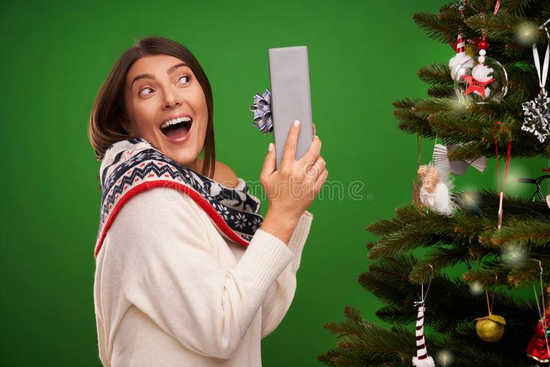 Adult happy woman with Christmas gift over green background. Picture of adult happy woman with Christmas gift stock photography