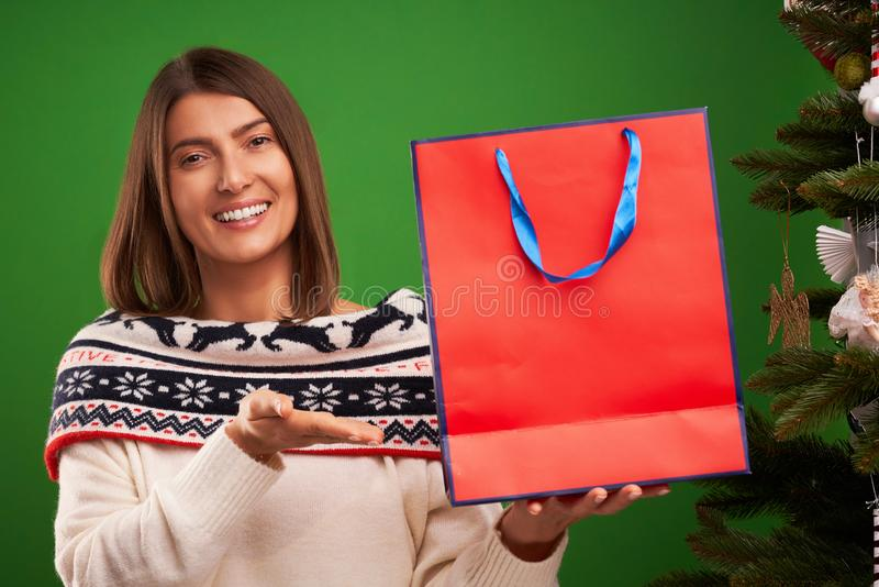 Adult happy woman shopping for Christmas presents over green background royalty free stock photos