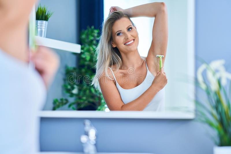 Beautiful woman shaving armpits in the bathroom. Picture of adult woman in the bathroom stock image
