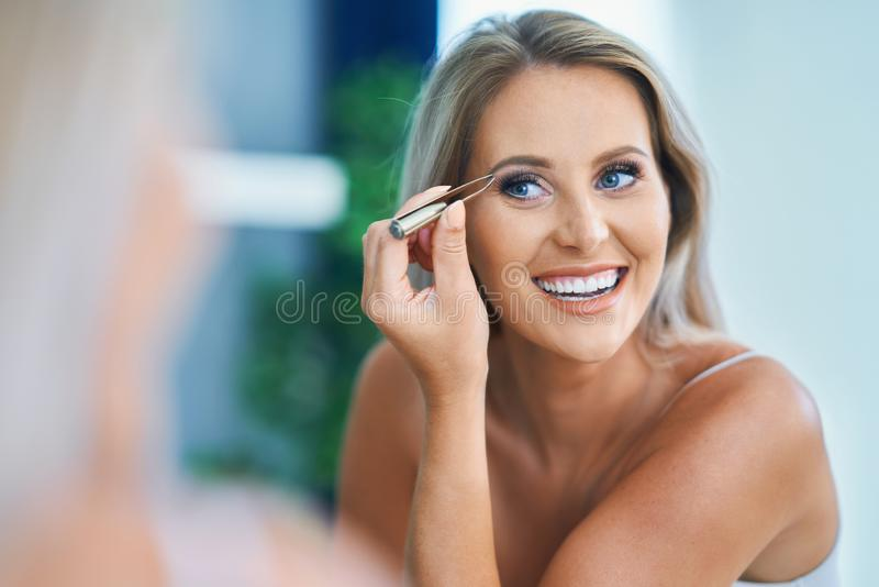 Beautiful woman with tweezers in the bathroom. Picture of adult woman in the bathroom stock photo