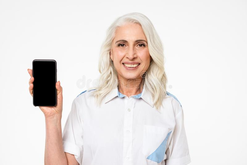 Picture of adult woman with grey hair smiling and doing commercial with presenting mobile phone, isolated over white background stock photo