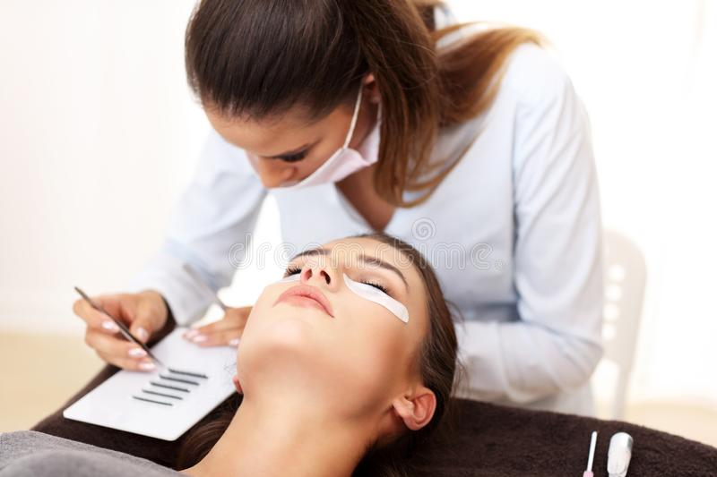 Adult woman having eyelash extension in professional beauty salon. Picture of adult women having eyelash extension in professional beauty salon royalty free stock photos