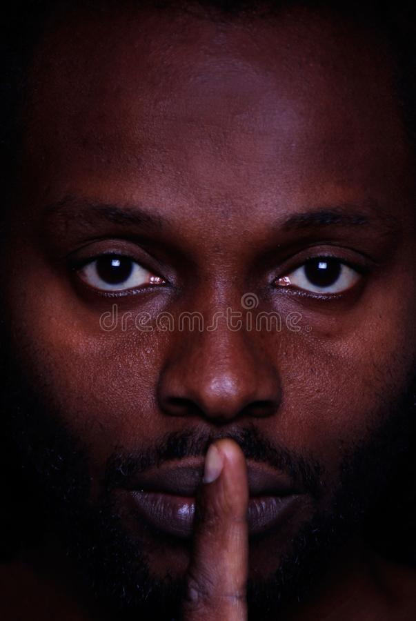 A picture of an African man looking at you with a finger across his lips royalty free stock photos