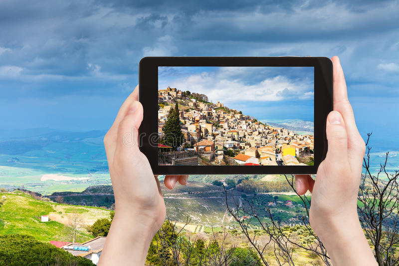 Picture of Aidone town in Sicily. Travel concept - tourist takes picture of Aidone town in Sicily in spring, Italy on tablet pc royalty free stock photography