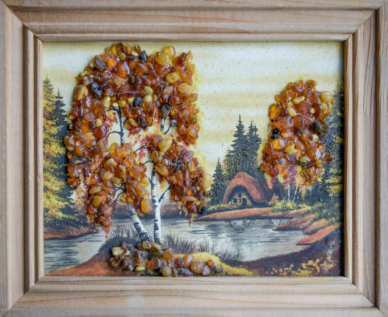 Picture of an amber stone. Crafts made of amber. Landscape house by the river stock photography