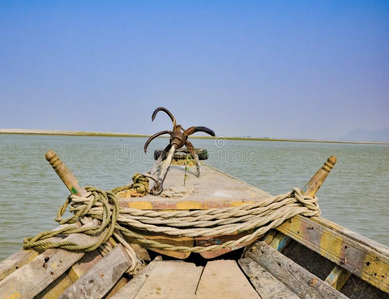 Picture of an anchor in the front of a boat in a river..with ropes and a tire.. Riverwith, yellowboat, village, picnic, water, horizon, green, field royalty free stock photo