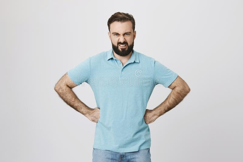 Picture of an angry bearded man holding his arms on waist. Body language and emotions concept. Male is fed up of his royalty free stock photo