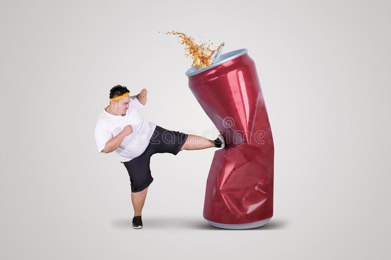 Angry fat man kicking a can of soda drink. Picture of angry fat man kicking a can of soda drink while wearing sportswear in the studio, isolated on white royalty free stock images
