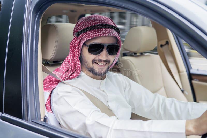 Happy Arabian businessman driving a new car stock photography