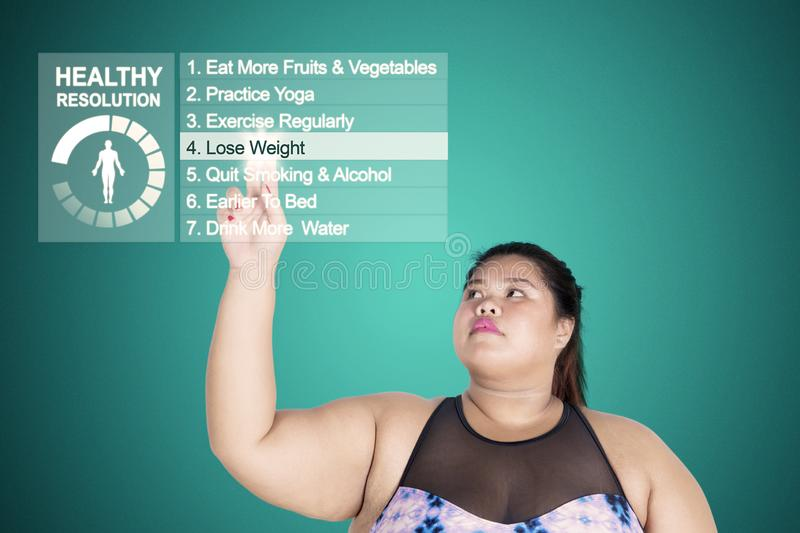 Asian fat woman touches a button of lose weight. Picture of Asian fat woman touching a button of lose weight in the virtual screen stock photo