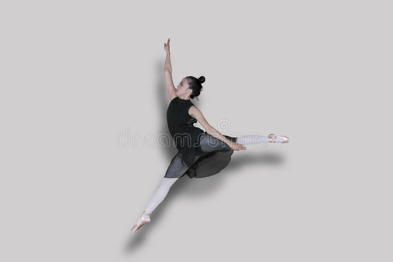 Ballet dancer doing jump exercises with graceful poses in studio. Picture of an Asian female ballet dancer doing jump exercises with graceful poses in the studio royalty free stock images