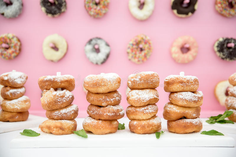 Picture of assorted donuts in a box with chocolate frosted, pink glazed and sprinkles donuts. stock image