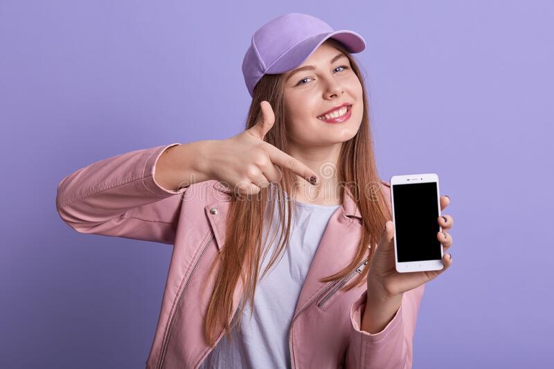 Picture of attractive charismatic sweet girl pointing with forefinger at device, holding smartphone with blank screen in one hand. Making presentation royalty free stock photo