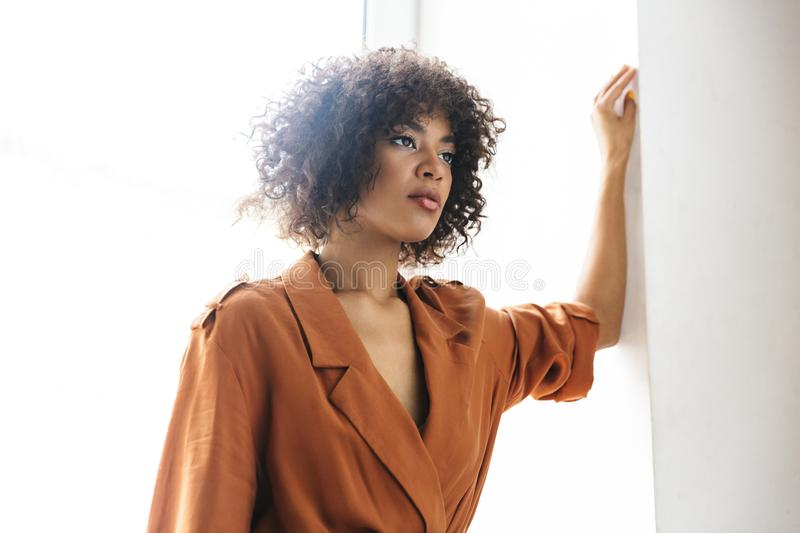 Picture of Attractive pretty african woman looking away while posing. Near the window stock image
