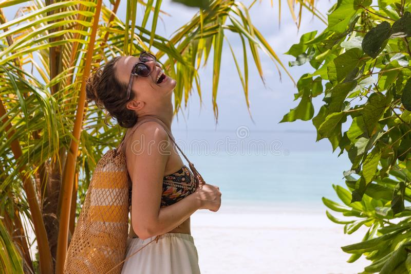 Young happy woman with a towel walking to the beach in a tropical destination. Laughing to the camera royalty free stock images