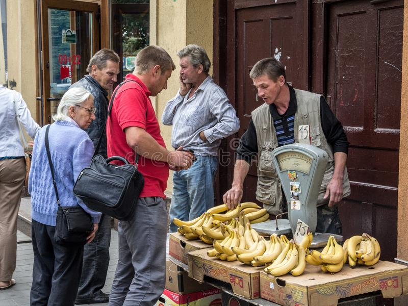 Banana seller on a stand on Lviv market Rinok with people buying them. A vintage scale is visible on the foreground stock photography
