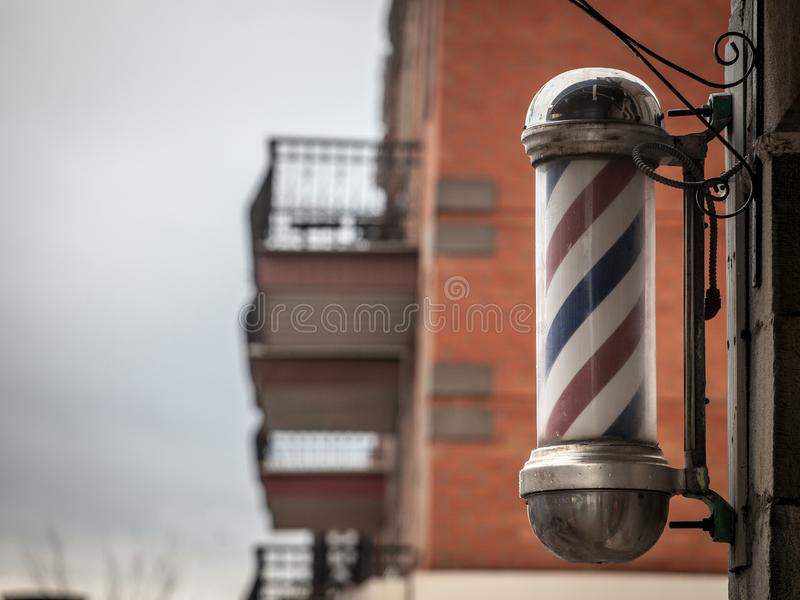 Typical American barbers pole seen in front of a barber shop of Montreal, Canada. stock photo