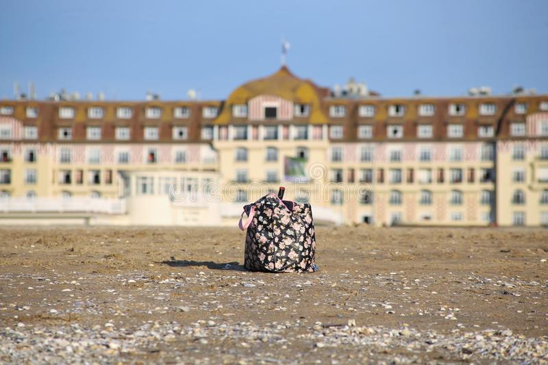 Picture of a beach bag with toys in Normandy symbolizing a week-end at the sea in France. An bag in a blurry background on the beach, symbolizing a week-end of royalty free stock photos
