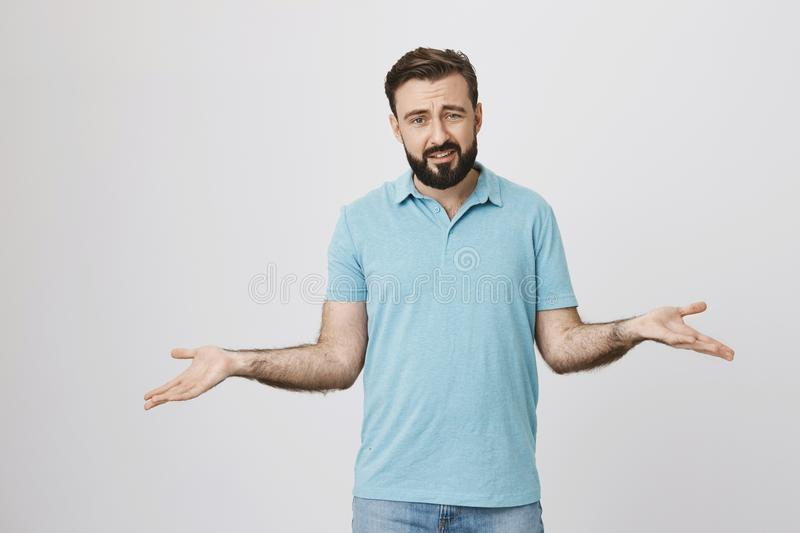 Picture of bearded handsome man looking questioned standing with spread hands over white background. Middle aged guy do royalty free stock photo