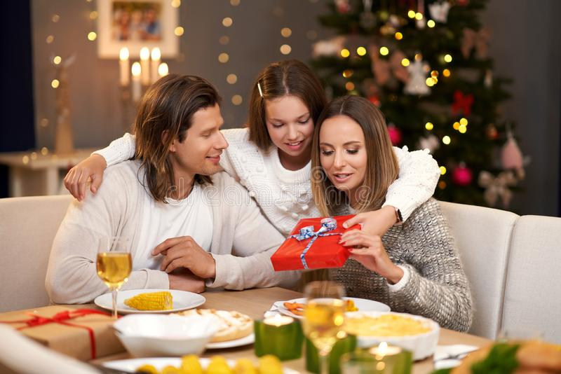 Beautiful family with presents sharing presents during Christmas dinner stock photos