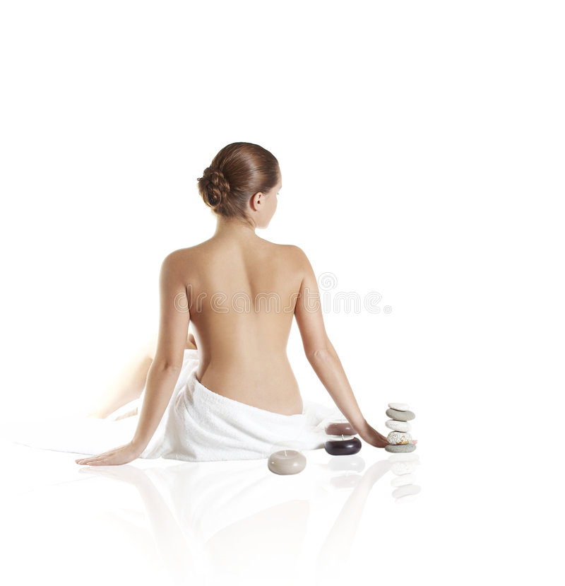 Picture of beautiful lady with wite towels. The perfect woman sits by a back about aromatic candles royalty free stock images