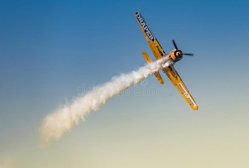 YAK-52 , Aerobatic Yakkers. Picture with beautiful old plane Yak 52tw flying on blue sky at aieshow from Romania royalty free stock photography