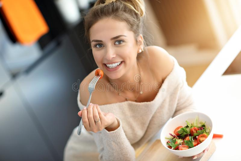 Beautiful Smiling Woman Eating Fresh Organic Vegetarian Salad In Modern Kitchen royalty free stock photos