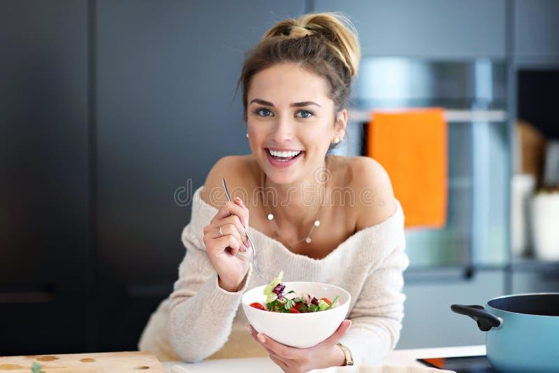 Beautiful Smiling Woman Eating Fresh Organic Vegetarian Salad In Modern Kitchen stock images