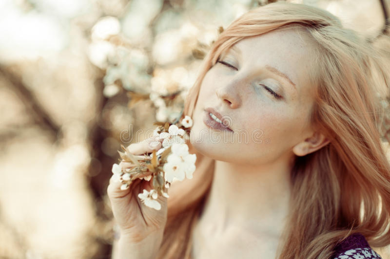 Picture of beautiful woman inhales the smell of spring. Outdoors stock photos
