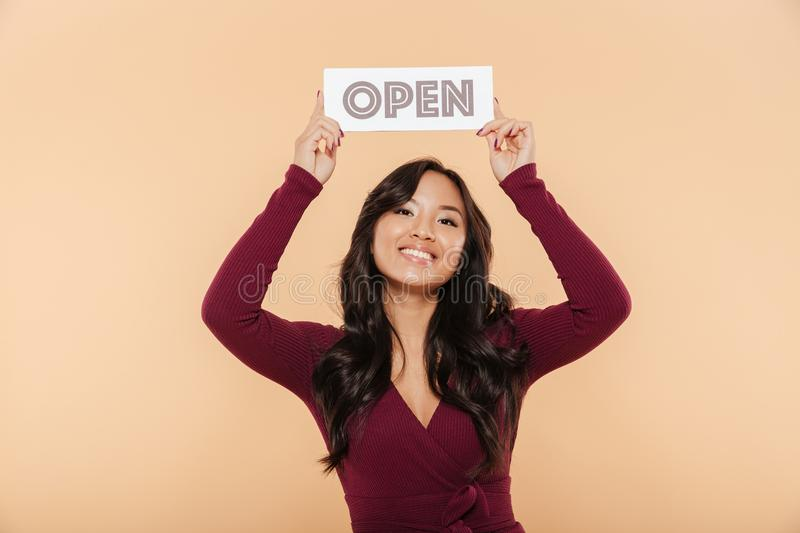 Picture of beautiful woman in maroon dress holding sign with word open over head being friendly on peach background. Picture of beautiful woman in maroon dress royalty free stock images