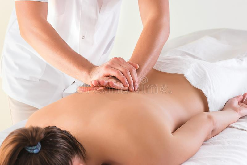 The picture of beautiful woman in massage salon. And male hands close up royalty free stock photo