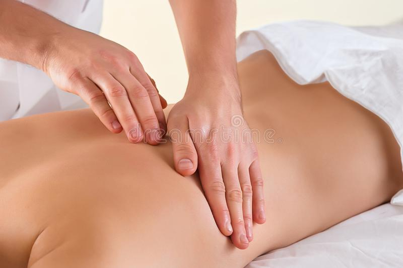 The picture of beautiful woman in massage salon. And male hands close up royalty free stock image