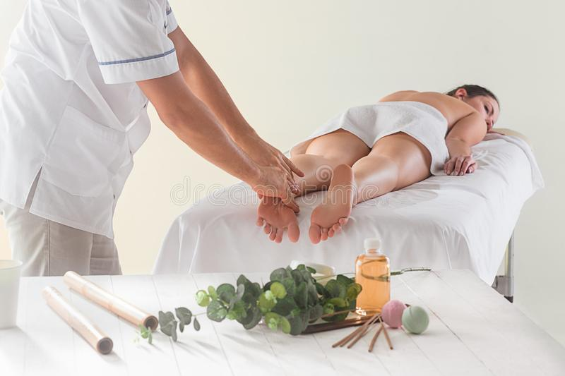 The picture of beautiful woman in massage salon. And male hands close up stock images