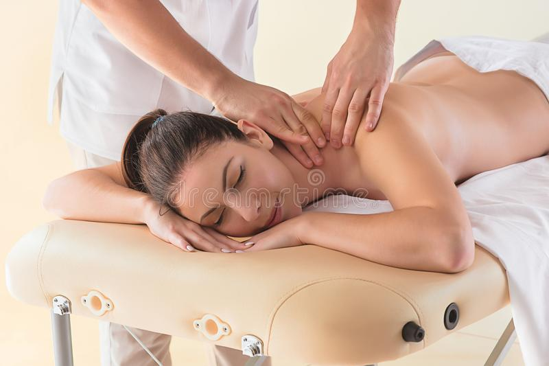 The picture of beautiful woman in massage salon. And male hands close up stock photos