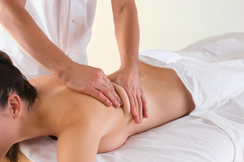 The picture of beautiful woman in massage salon. And male hands close up stock image
